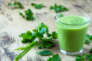 Green smoothie with parsley on wooden table